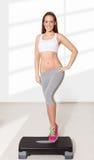 Νέα όμορφη γυναίκα που κάνει τις ασκήσεις με το αεροβικό βήμα στοκ εικόνα με δικαίωμα ελεύθερης χρήσης