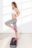 Νέα όμορφη γυναίκα που κάνει τις ασκήσεις με το αεροβικό βήμα στοκ εικόνα
