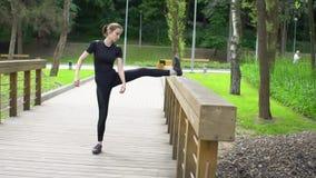 Νέα όμορφη γυναίκα που κάνει τις τεντώνοντας ασκήσεις στο πάρκο σε αργή κίνηση φιλμ μικρού μήκους