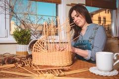 Νέα όμορφη γυναίκα που κατασκευάζει τα καλάθια Στοκ Φωτογραφία