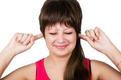 Νέα όμορφη γυναίκα που καλύπτει τα αυτιά της. απομονωμένος Στοκ Φωτογραφία
