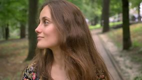 Νέα όμορφη γυναίκα που κοιτάζει γύρω από και που περπατά στην οδό με τη χλόη και τα δέντρα παντού, ευτυχής και που γοητεύει απόθεμα βίντεο