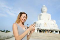 Νέα όμορφη γυναίκα που κουβεντιάζει από το smartphone κοντά στο άσπρο άγαλμα του Βούδα σε Phuket Στοκ Φωτογραφίες