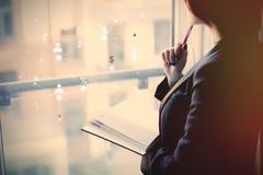 Νέα όμορφη γυναίκα που κρατά ένα σημειωματάριο και που σκέφτεται κοντά στο W Στοκ Φωτογραφίες