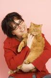 Νέα όμορφη γυναίκα που κρατά μια κόκκινη εσωτερική γάτα Στοκ εικόνα με δικαίωμα ελεύθερης χρήσης