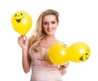 Νέα όμορφη γυναίκα που κρατά τα κίτρινα μπαλόνια smiley, valentine Στοκ Εικόνες