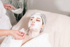 Νέα όμορφη γυναίκα που λαμβάνει τις επεξεργασίες στα σαλόνια ομορφιάς Νέα όμορφη σκοτεινός-μαλλιαρή γυναίκα στο beautician γραφεί Στοκ εικόνες με δικαίωμα ελεύθερης χρήσης