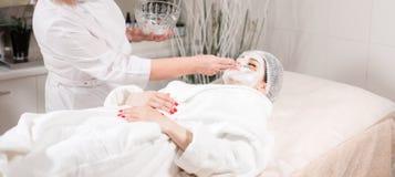 Νέα όμορφη γυναίκα που λαμβάνει τις επεξεργασίες στα σαλόνια ομορφιάς Νέα όμορφη σκοτεινός-μαλλιαρή γυναίκα στο beautician γραφεί Στοκ Εικόνες