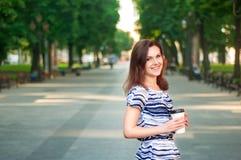 Νέα όμορφη γυναίκα που μένει στο πάρκο με τον καφέ σε την Στοκ Εικόνες