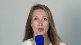 Νέα όμορφη γυναίκα που μιλά με το μικρόφωνο απόθεμα βίντεο