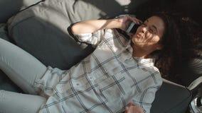 Νέα όμορφη γυναίκα που μιλά στο κινητό τηλέφωνο στο καλό σπίτι φιλμ μικρού μήκους