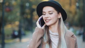 Νέα όμορφη γυναίκα που μιλά στο κινητό τηλέφωνό της περπατώντας στο πάρκο φθινοπώρου σε ένα υπόβαθρο των κίτρινων φύλλων απόθεμα βίντεο