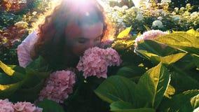 Νέα όμορφη γυναίκα που μυρίζει τα ρόδινα λουλούδια φιλμ μικρού μήκους