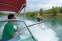 Νέα όμορφη γυναίκα που οδηγά wakeboard motorboat κυμάτων Στοκ Εικόνες