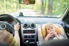 Νέα όμορφη γυναίκα που οδηγεί ένα αυτοκίνητο Σε ένα μέτωπο το κάθισμα τοποθέτησε το κάθισμα ασφάλειας παιδιών με ένα αρκετά 1χρον στοκ φωτογραφία με δικαίωμα ελεύθερης χρήσης