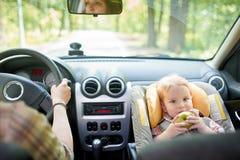 Νέα όμορφη γυναίκα που οδηγεί ένα αυτοκίνητο Σε ένα μέτωπο το κάθισμα τοποθέτησε το κάθισμα ασφάλειας παιδιών με ένα αρκετά 1χρον στοκ εικόνα με δικαίωμα ελεύθερης χρήσης