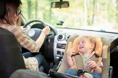 Νέα όμορφη γυναίκα που οδηγεί ένα αυτοκίνητο Σε ένα μέτωπο το κάθισμα τοποθέτησε το κάθισμα ασφάλειας παιδιών με ένα αρκετά 1χρον στοκ εικόνες