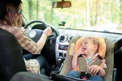 Νέα όμορφη γυναίκα που οδηγεί ένα αυτοκίνητο Σε ένα μέτωπο το κάθισμα τοποθέτησε το κάθισμα ασφάλειας παιδιών με ένα αρκετά 1χρον στοκ εικόνες με δικαίωμα ελεύθερης χρήσης