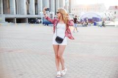 Νέα όμορφη γυναίκα που παίρνει ένα selfie στο τετράγωνο στην πόλη Στοκ Φωτογραφία