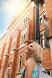 Νέα όμορφη γυναίκα που περπατά κάτω από την οδό κατά μήκος ενός παλαιού κτηρίου τούβλου στα πλαίσια του φωτός του ήλιου Στοκ εικόνα με δικαίωμα ελεύθερης χρήσης