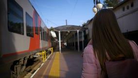 Νέα όμορφη γυναίκα που περπατά κατά μήκος του σταθμού τρένου κατά μήκος του τραίνου απόθεμα βίντεο