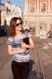 Νέα όμορφη γυναίκα που περπατά στην πόλη πρωινού με ένα βιβλίο Στοκ Φωτογραφία