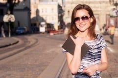 Νέα όμορφη γυναίκα που περπατά στην πόλη πρωινού με ένα βιβλίο Στοκ Εικόνες