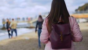 Νέα όμορφη γυναίκα που περπατά στη θάλασσα απόθεμα βίντεο