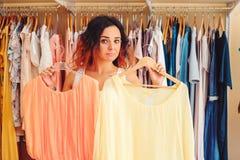 Νέα όμορφη γυναίκα που προσπαθεί στο νέο φόρεμα στο κατάστημα ιματισμού Αγορές Στοκ φωτογραφία με δικαίωμα ελεύθερης χρήσης