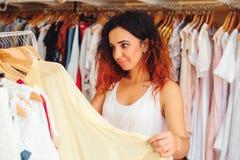Νέα όμορφη γυναίκα που προσπαθεί στο νέο φόρεμα στο κατάστημα ιματισμού Αγορές Στοκ Εικόνες