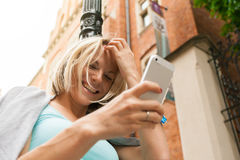 Νέα όμορφη γυναίκα που στέκεται με το κινητό τηλέφωνο στα πλαίσια του παλαιού κτηρίου τούβλου Στοκ φωτογραφία με δικαίωμα ελεύθερης χρήσης