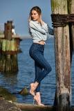 Νέα όμορφη γυναίκα που στέκεται στην αποβάθρα στη μαρίνα βαρκών Στοκ Εικόνες
