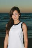 Νέα όμορφη γυναίκα που στέκεται στην παραλία στο ηλιοβασίλεμα Στοκ Φωτογραφία