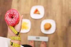 Νέα όμορφη γυναίκα που στέκεται στις κλίμακες και που κρατά doughnut κατανάλωση έννοιας υγιής Υγιής τρόπος ζωής σιτηρέσιο Στοκ Φωτογραφίες
