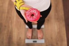Νέα όμορφη γυναίκα που στέκεται στις κλίμακες και που κρατά doughnut κατανάλωση έννοιας υγιής Υγιής τρόπος ζωής σιτηρέσιο Στοκ Εικόνες