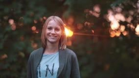 Νέα όμορφη γυναίκα που στέκεται στο πάρκο στις ακτίνες του ήλιου ρύθμισης, χαμόγελο και γέλιο, που κοιτάζουν στη κάμερα απόθεμα βίντεο