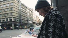 Νέα όμορφη γυναίκα που ταξιδεύει με έναν χάρτη στις οδούς πόλεων φιλμ μικρού μήκους