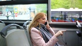 Νέα όμορφη γυναίκα που ταξιδεύει με το λεωφορείο επίσκεψης τουριστών, με το έξυπνο τηλέφωνο φιλμ μικρού μήκους