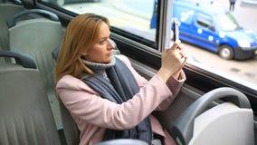Νέα όμορφη γυναίκα που ταξιδεύει με το λεωφορείο επίσκεψης τουριστών, με το έξυπνο τηλέφωνο απόθεμα βίντεο