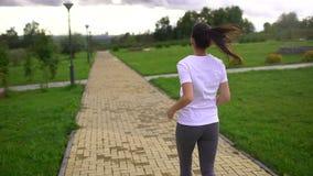 Νέα όμορφη γυναίκα που τρέχει στο πάρκο Λήφθείτε από την πλάτη Σε αργή κίνηση απόθεμα βίντεο