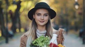 Νέα όμορφη γυναίκα που φορά το μοντέρνο παλτό που περπατά στο πάρκο που κρατά μια συσκευασία των προϊόντων που χαμογελούν και που φιλμ μικρού μήκους