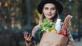 Νέα όμορφη γυναίκα που φορά το μοντέρνο παλτό που στέκεται στη συσκευασία εκμετάλλευσης πάρκων φθινοπώρου των προϊόντων και που χ φιλμ μικρού μήκους