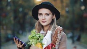 Νέα όμορφη γυναίκα που φορά το μοντέρνο παλτό που στέκεται στη συσκευασία εκμετάλλευσης πάρκων φθινοπώρου των προϊόντων και που χ απόθεμα βίντεο
