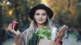 Νέα όμορφη γυναίκα που φορά το μοντέρνο παλτό που στέκεται στο πάρκο που κρατά μια συσκευασία των προϊόντων που χαμογελούν και πο απόθεμα βίντεο