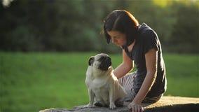 Νέα όμορφη γυναίκα που φυσά ένα φιλί στο σκυλί της στο πάρκο, χαριτωμένα Mop που φιλά μια συνεδρίαση κοριτσιών, σκυλιών και ιδιοκ απόθεμα βίντεο