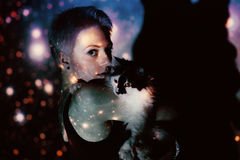 Νέα όμορφη γυναίκα που χάνεται στο διάστημα γύρω από τα αστέρια με τη γάτα Στοκ Εικόνες