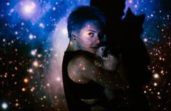 Νέα όμορφη γυναίκα που χάνεται στο διάστημα γύρω από τα αστέρια με τη γάτα Στοκ εικόνες με δικαίωμα ελεύθερης χρήσης