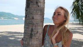 Νέα όμορφη γυναίκα που χαμογελά και που στέλνει το φιλί αέρα κοντά στο δέντρο φοινικών στο μπλε υπόβαθρο θάλασσας Ρομαντική έννοι απόθεμα βίντεο