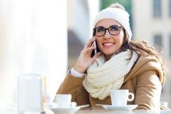 Νέα όμορφη γυναίκα που χρησιμοποιεί το κινητό τηλέφωνό της σε έναν καφέ Στοκ Φωτογραφία