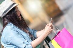 Νέα όμορφη γυναίκα που χρησιμοποιεί το τηλέφωνο της Mobil μετά από να ψωνίσει, ελαφριά επίδραση Στοκ Εικόνες